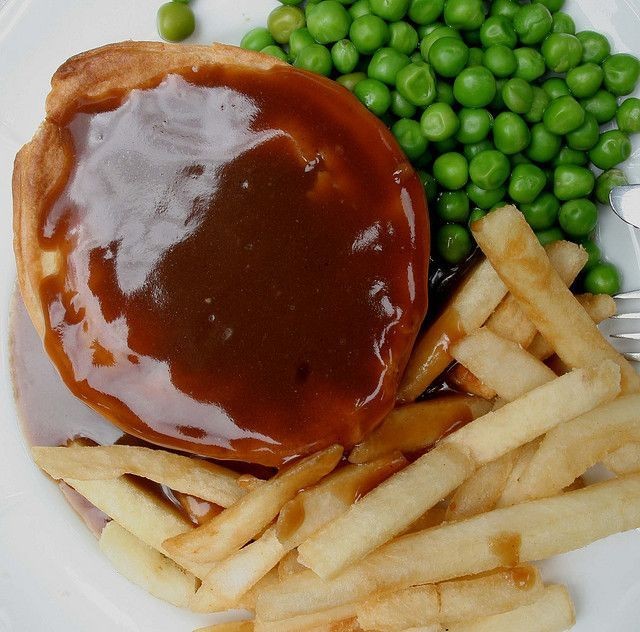 Steak or beef pie with chips or fries and green peas.