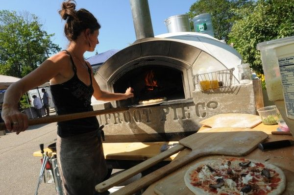 Jessica Shepard Puts A Pizza Into Her Portable Wood Fired Pizza Oven At The  Camden