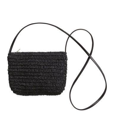 Lille skuldertaske i flettet papirstrå. Tasken har lynlås foroven og skulderrem i imiteret læder. Foret. Størrelse 18x22 cm.
