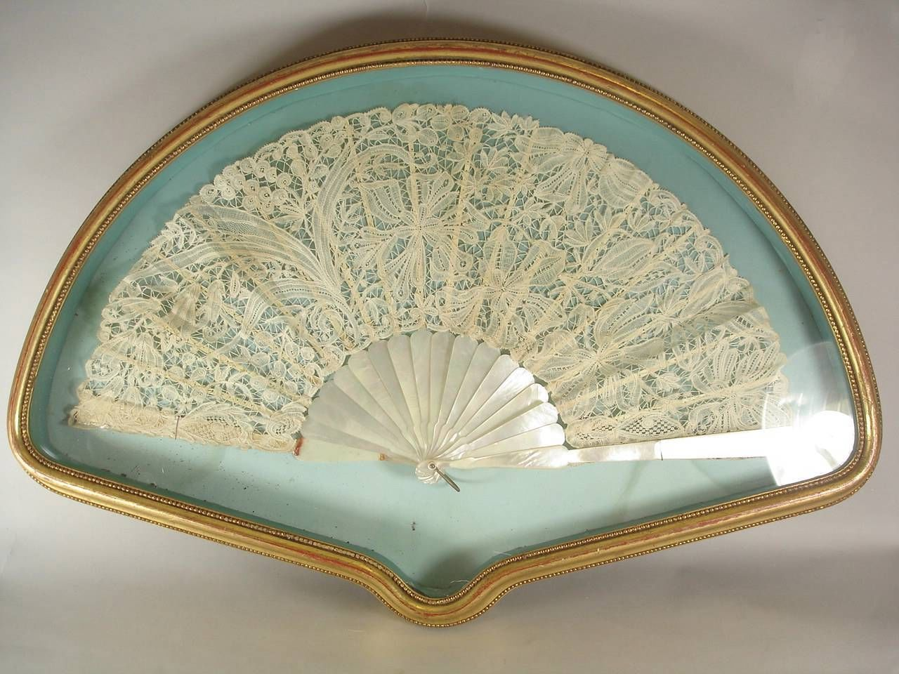 Exquisite 19th Century Mother of Pearl lace fan within a gilt shadow box.