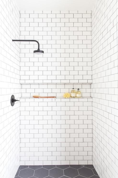 An Oil Rubbed Bronze Shower Head Is Fixed To White Subway Shower Surround Tiles Accented With B White Tile Shower White Bathroom Tiles White Subway Tile Shower