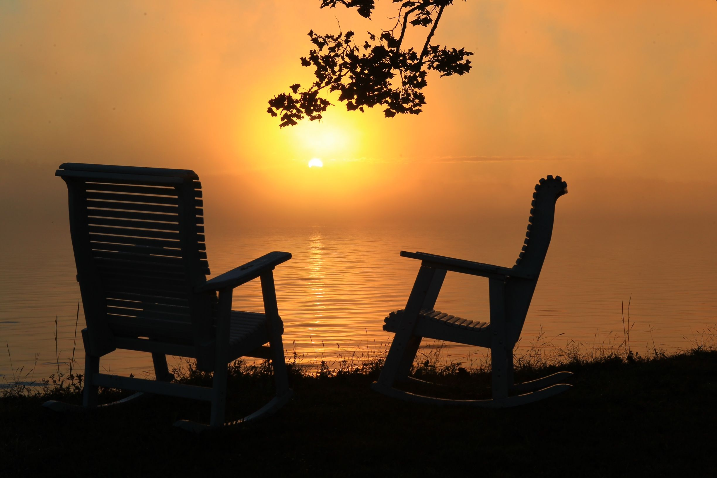 Two rocking chairs bathed in sunrise on Watts Bar Lake in