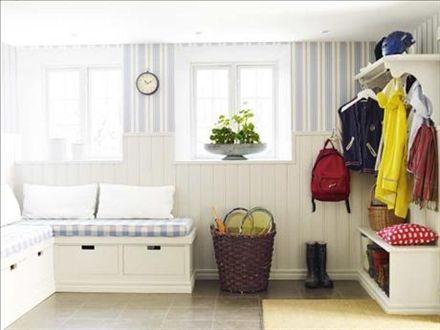 Bara de mest aktuella ytterkläderna hänger framme. Resten förvaras i en garderobsvägg i rummet intill. Nedre delen av väggen är täckt av vitmålad pärlspont, som är lätt att torka av. Den blåvitrandiga tapeten kommer från Ralph Lauren/Gåvan. Väggklockan, privat, hjälper till att hålla tiden när man ska iväg.  Praktiska platsbyggda sittbänkar med lådor under för vantar, mössor m m. Tyget och dynorna är från Gåvan. De röda elefantkuddarna är från Svenskt tenn.Golvet har klinker med golvvärme…