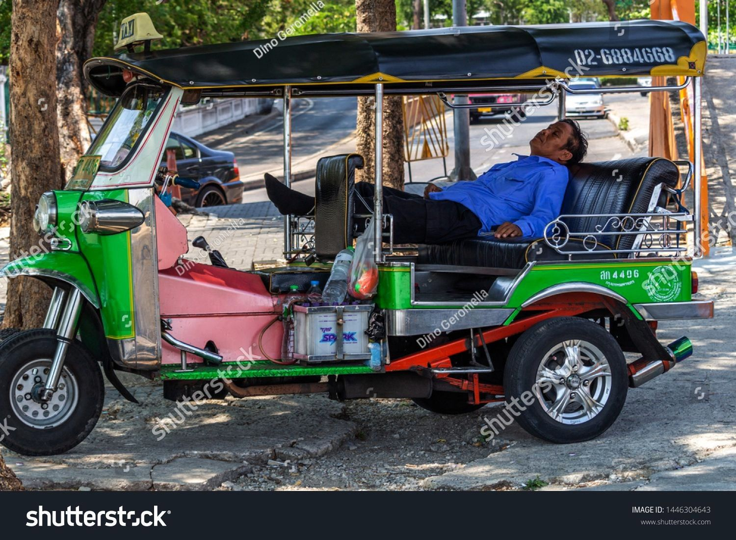 Thailand  April 14 2019 Taxi driver sleeping in his tuk tuk parked near the street Bangkok Thailand  April 14 2019 Taxi driver sleeping in his tuk tuk parked near the str...