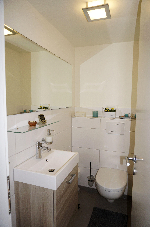 Ein waschtischmöbel aus holz und gedeckte farben machen das gäste wc zu einem angenehmen rückzugsort