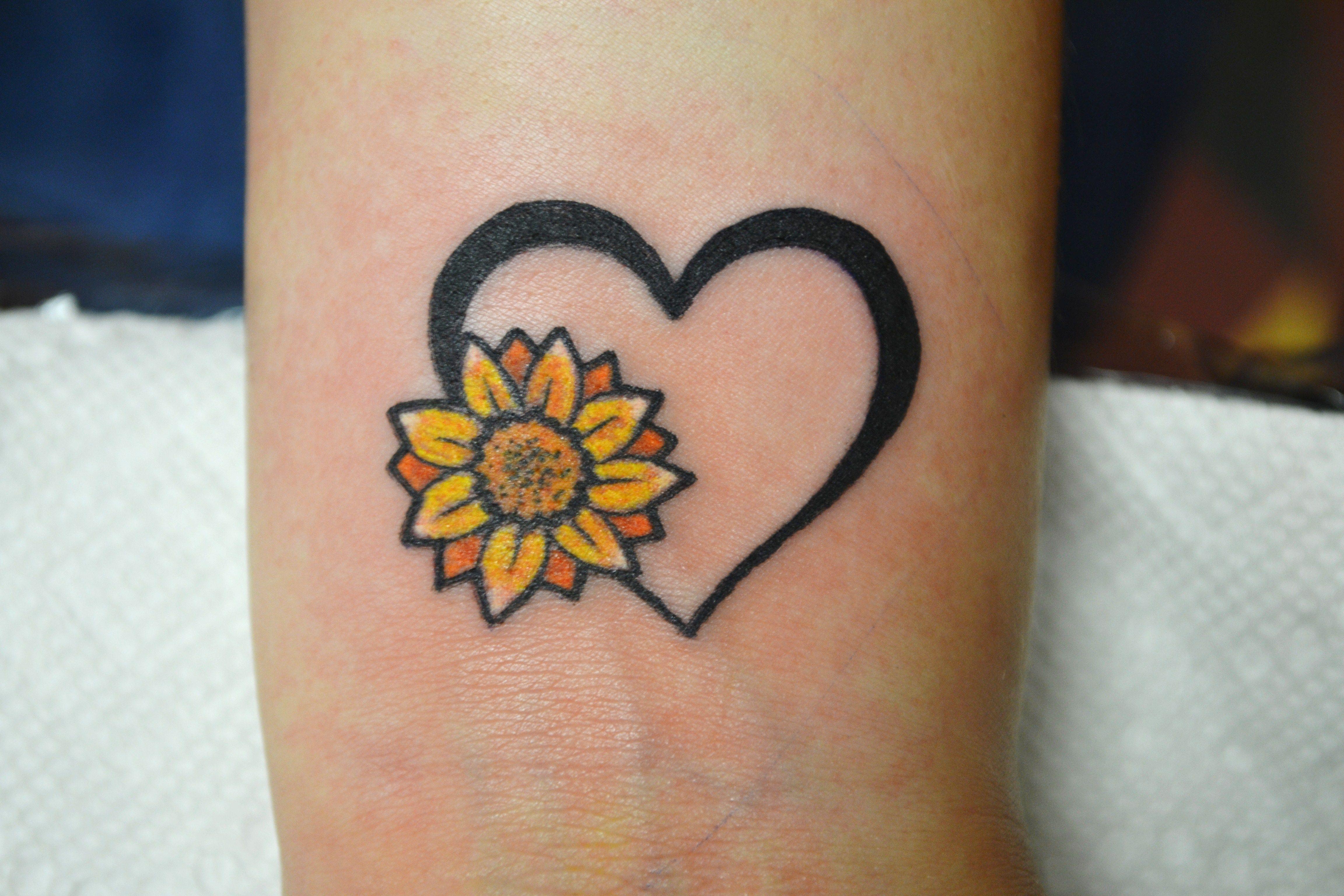 tiny tattoo sunflower heart wrist tattoo artist Adrienne