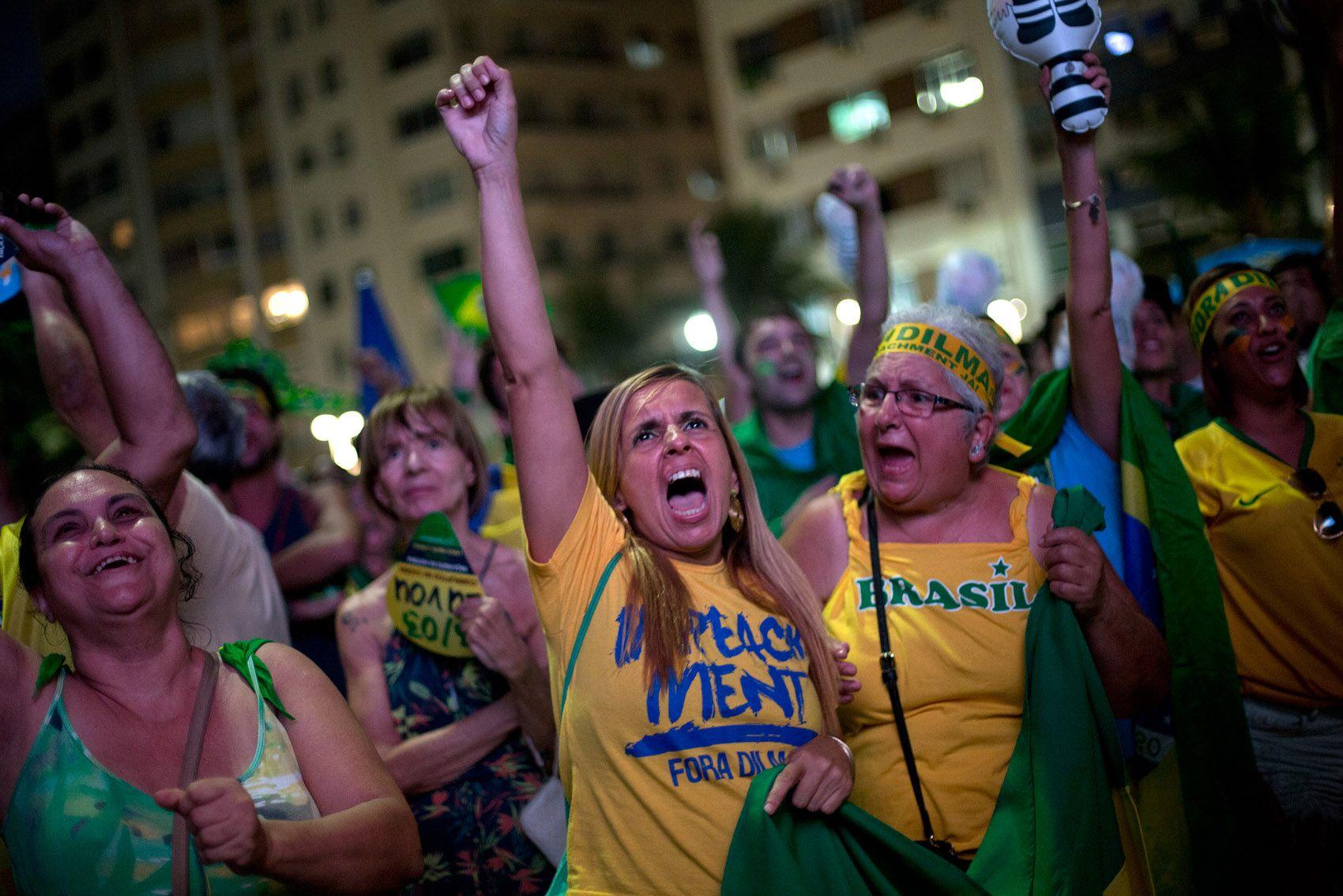 Manifestantes pró-impeachment comemoram enquanto assistem a votação do processo de impeachment em um telão instalado na praia de Copacabana, no Rio de Janeiro