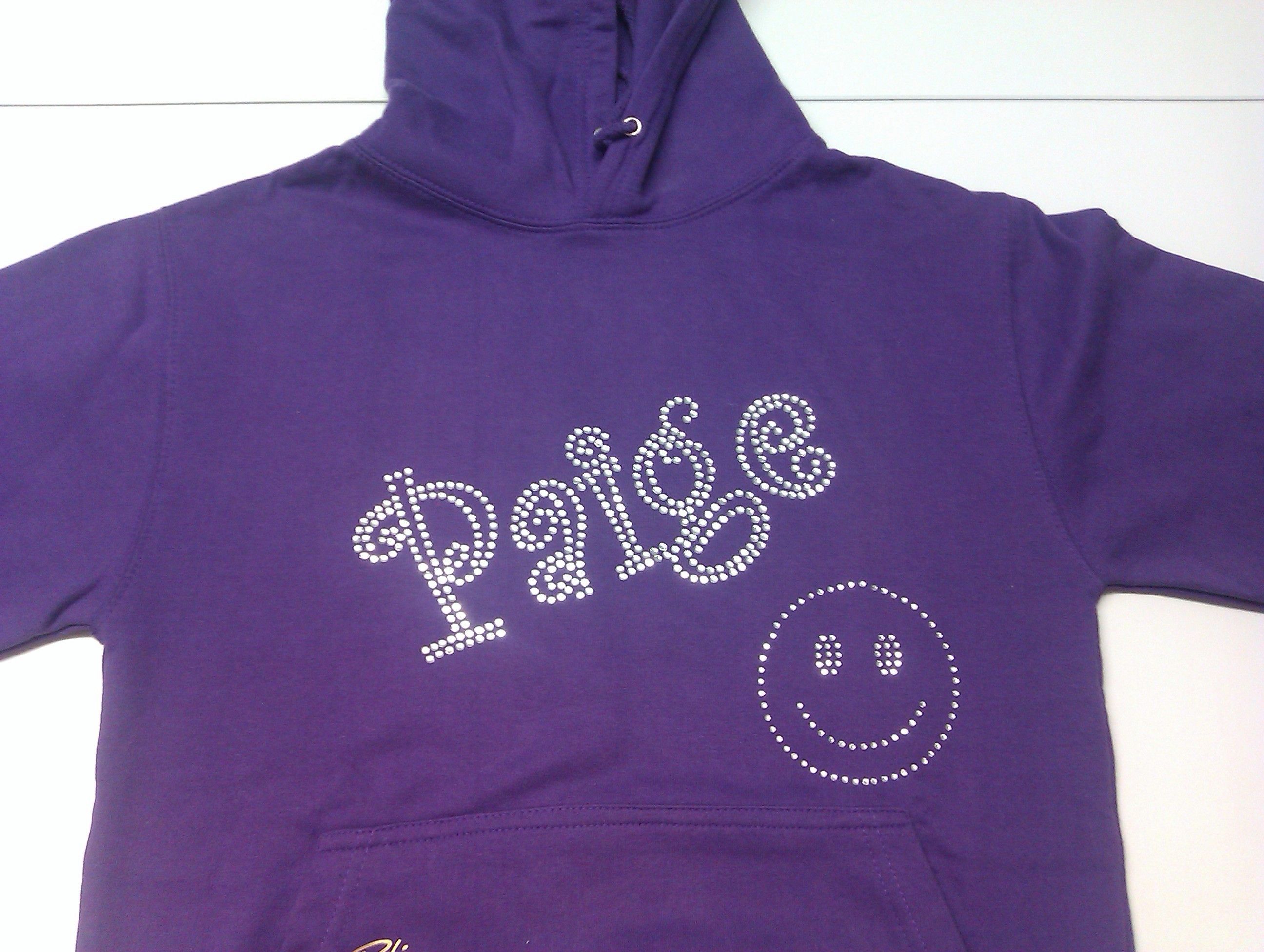 Deep purple Paige hoodie, written in clear bling in the curlz font, with a happy smiley face! For more pictures/info you can visit our website or give us a call!