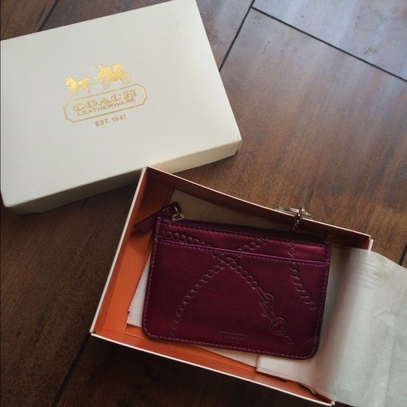 COACH Wallet Used a couple of times. It's in great condition. It has three slots on the inside for card, but you can put more than one card in each slot. Also it fits cash in there nicely. You can attach it to your key chain or any where else. It's purple and has chain detailing and the brand name on it. It comes with a box. If you have any questions, please feel free to ask! :) Coach Bags Wallets