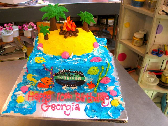 A4 Survivor themed cake with built-up island, fondant palm trees & fire, Survivor logo & fondant sea themed decor by Charly's Bakery, via Flickr