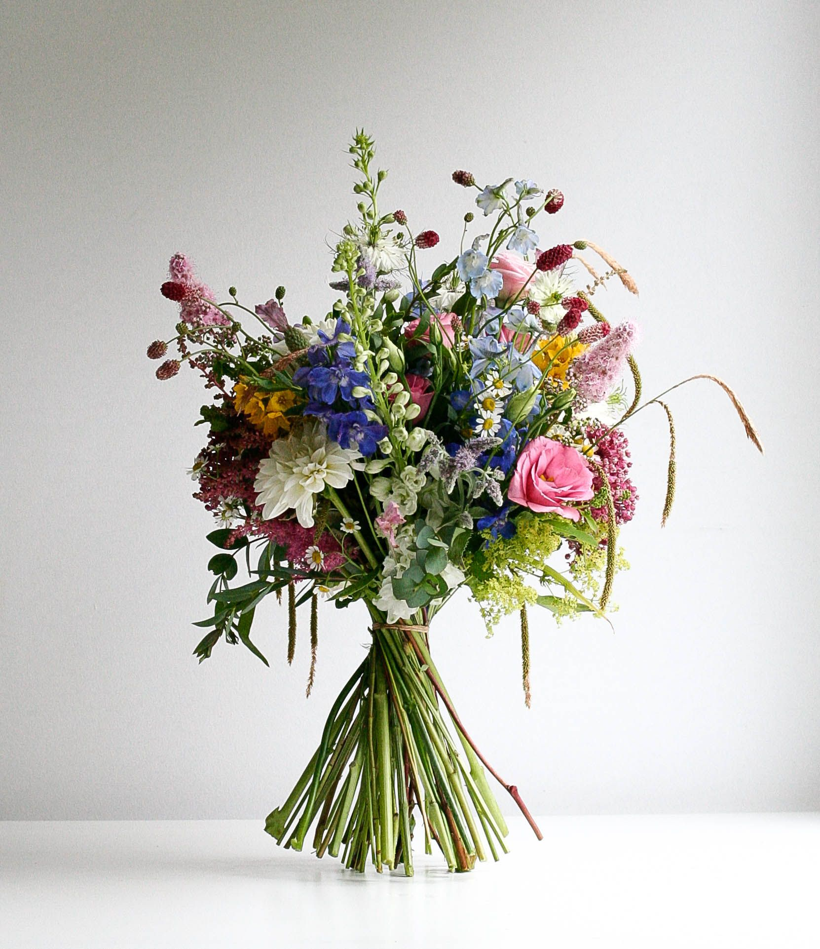 A wild meadow British Flowers brides bouquet. Using lots of different flowers that are not normally seen in a brides bouquet, mint , rosemary, chamomile, dahlia, delphinium, wild grass, French lavender #wildflowers