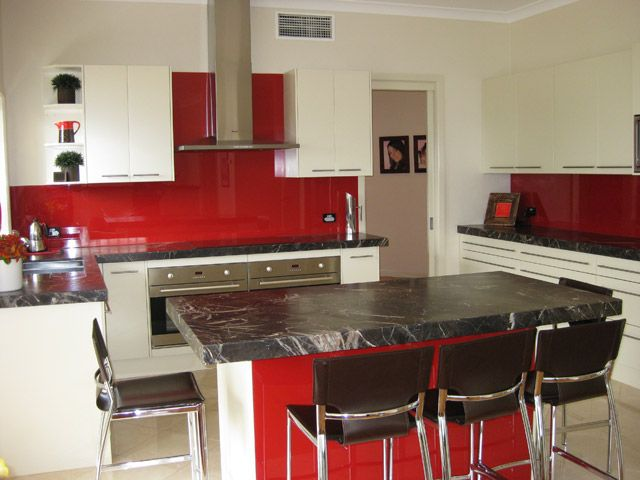 red splash back with black benchtop island and white cabinets ideas