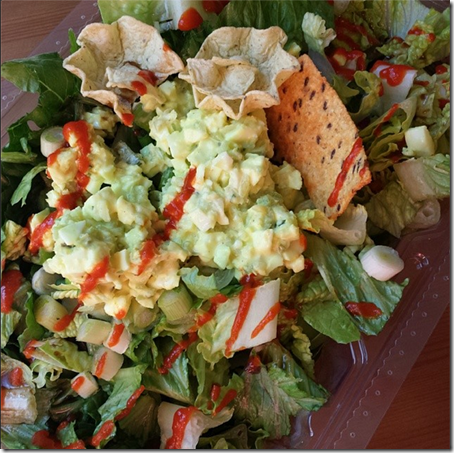 avocado egg salad on a bed of romaine lettuce, green onions, topped with hot sauce.