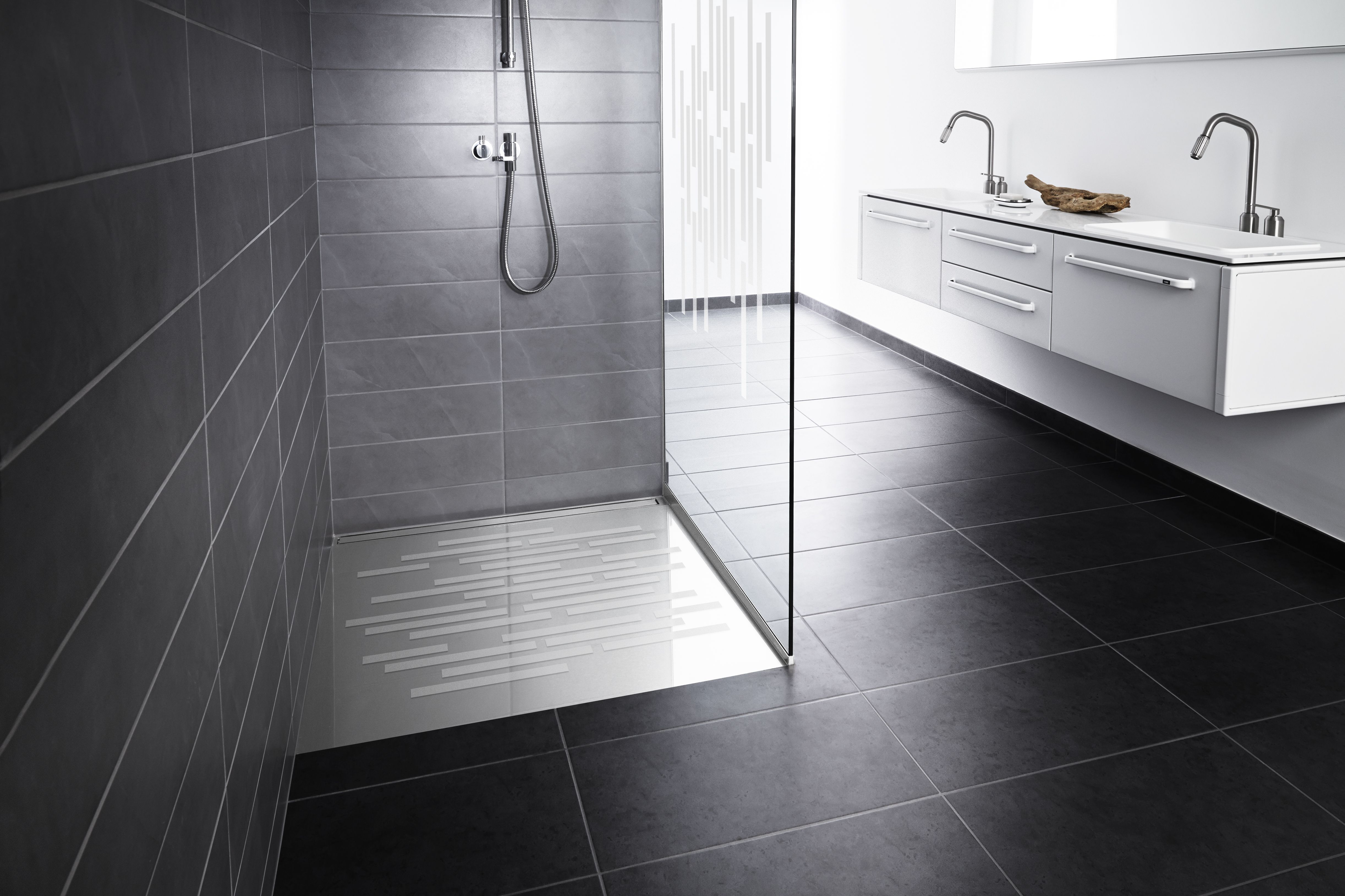 A stylish solution. Patented Linear Wall Mounted Drain with a solid stainless steel panel and Glass Shower Base along with an integrated glass shower screen. One slope no grout lines and no need to stand on the drain in the shower.