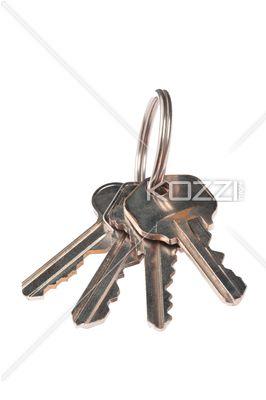 metallic keys on white background. - Close-up shot of metallic keys and key ring isolated over plain white background.