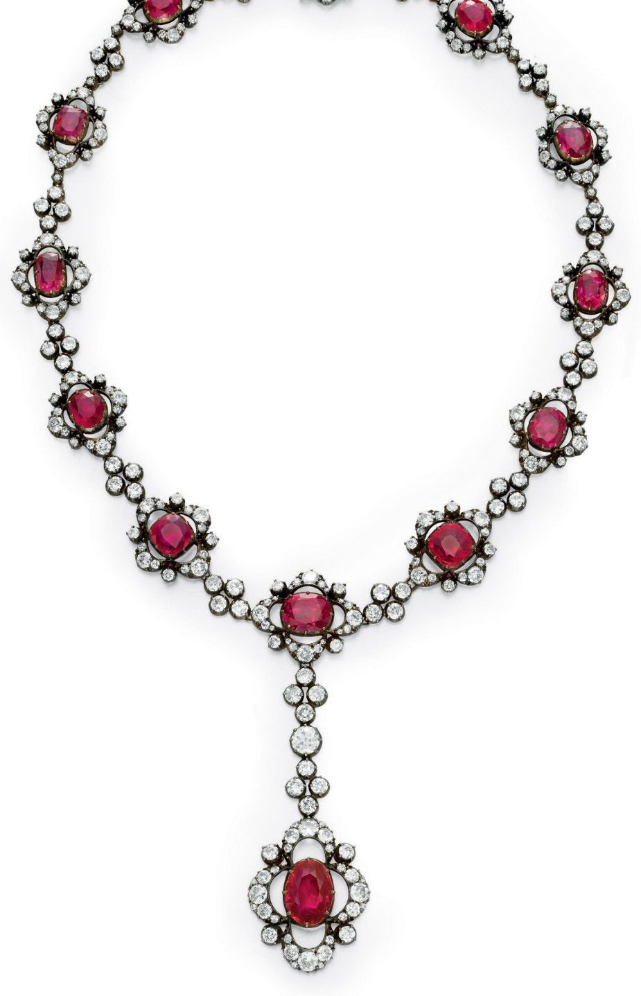 AN ANTIQUE RUBY AND DIAMOND NECKLACE. Suspending a bezel-set oval-cut ruby within an openwork old European and single-cut diamond scalloped surround, from a line of circular and old European-cut diamonds, to the neckchain, designed as a graduated series of bezel-set cushion-cut rubies, each within an openwork circular, old European and single-cut diamond scalloped surround, spaced by circular and old European-cut diamond clusters, mounted in silver-topped gold, circa 1880. #antique #necklace