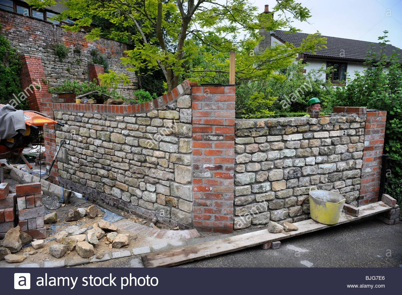 Download This Stock Image Building A Garden Wall With Cotswold Stone And Cement Mortar With Reclaimed Red Brick Pil Garden Wall Garden Images Garden Buildings