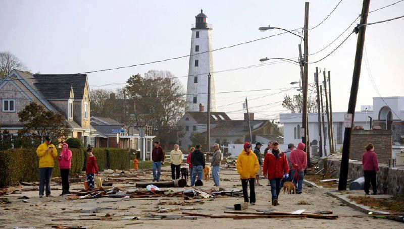 Residents survey the debris scattered on Pequot Ave. in New London, CT Tuesday morning.