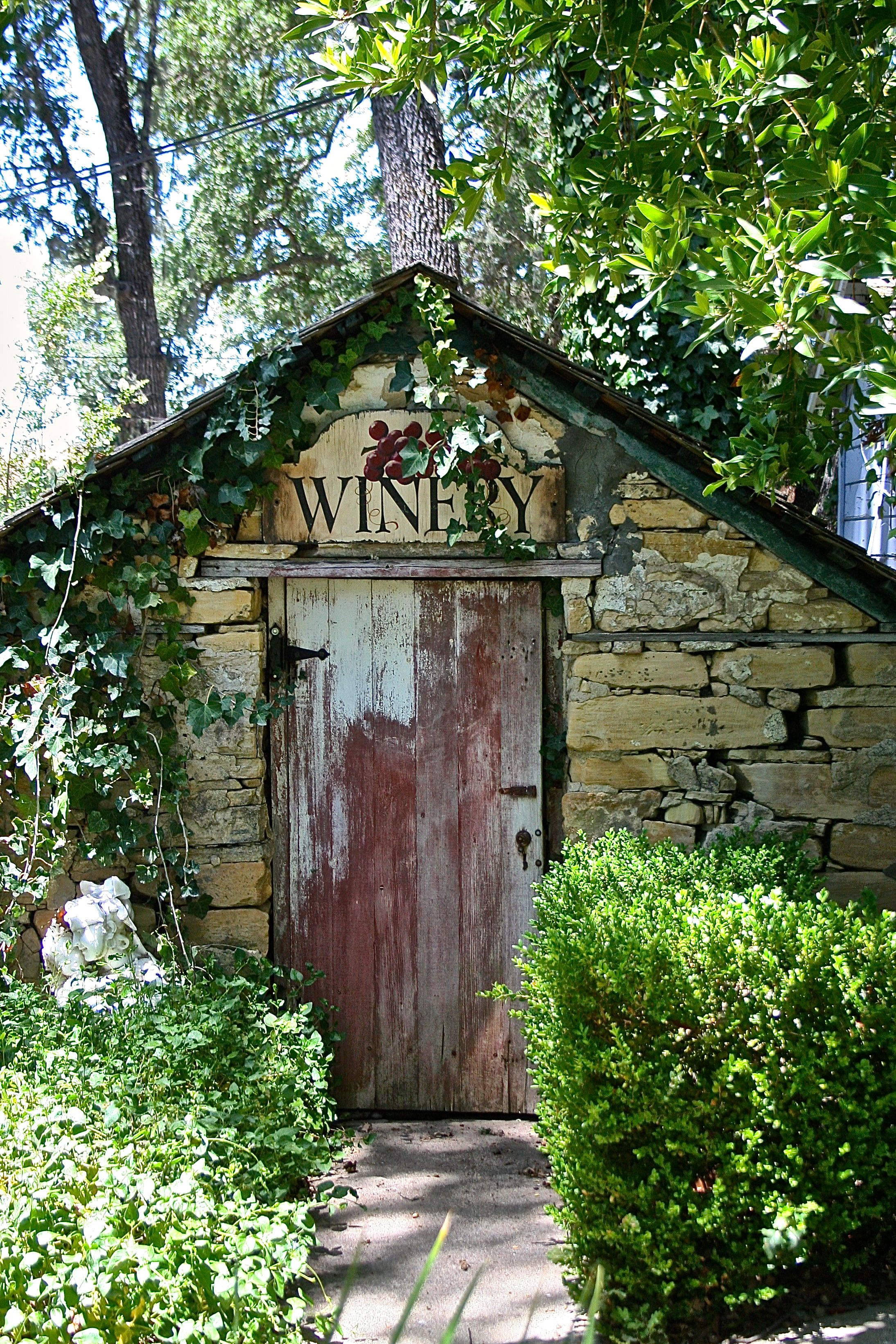 cool little wine basement weathered from time and mother nature.  love the old front door and sign.   ..rh