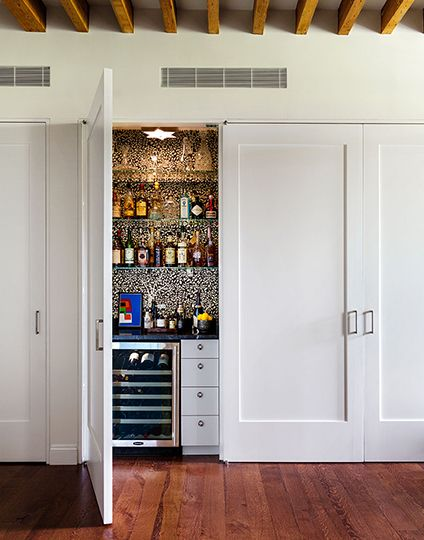 Living room features concealed bar hidden behind closet doors filled ...