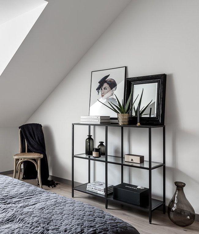 Neutralt inrett sovrum med svart metall bokhylla med aloe vera ...
