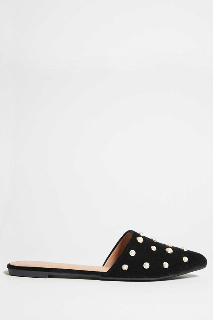 A pair of velvet slip-on mules by Yoki™ featuring a pointed toe, high-polish accented faux pearls on the vamp, and a low heel.