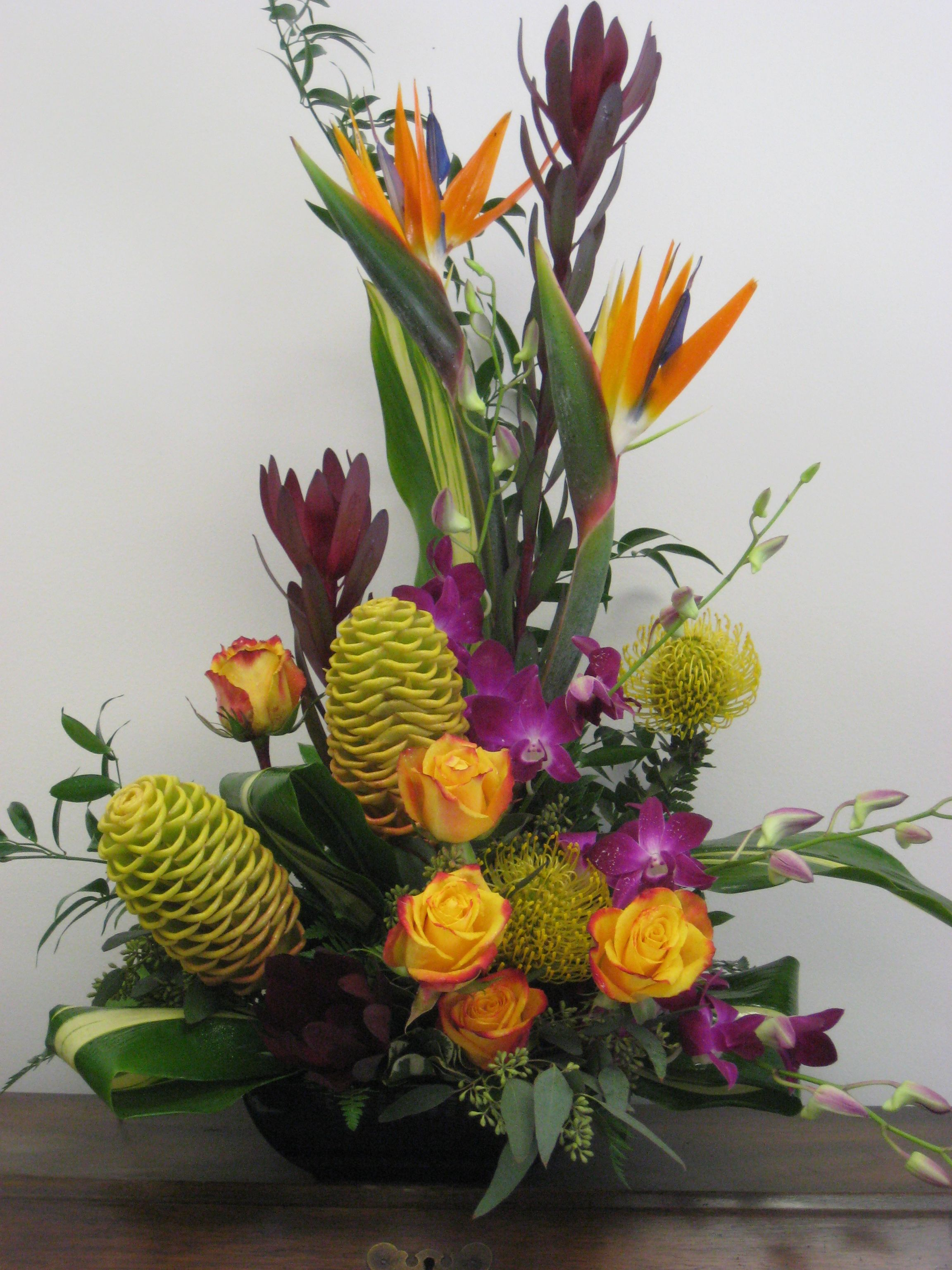 A striking color combination in tropicals - Beehive Ginger, Pincushion Protea, Dendrobium Orchids, Birds of Paradise and accented with the beautiful roses