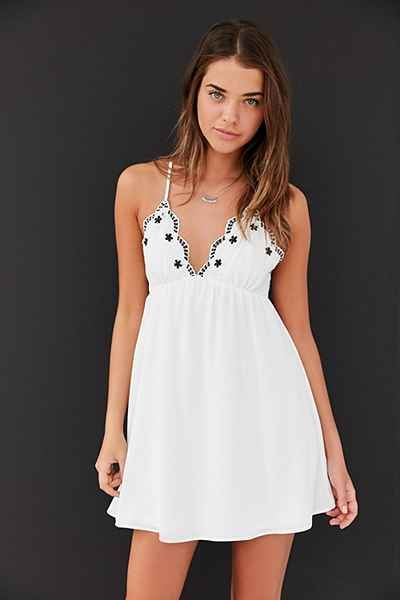 Floaty mini babydoll dress with an embroidered crochet-trim neckline, by Ecote. Sleeveless dress is topped with scalloped triangles + adjustable cross-straps. Finished with a hidden zip closure at the back.