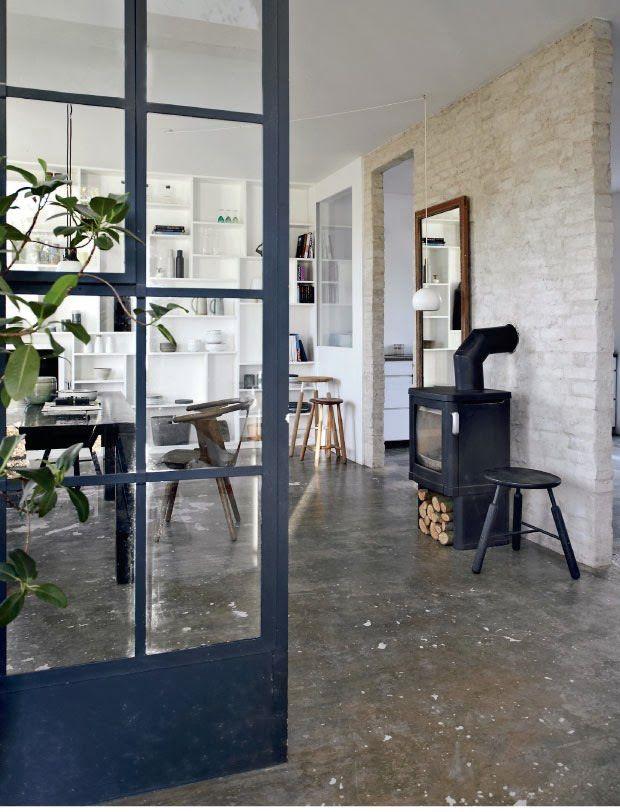 Vista del comedor con puerta de hierro y vidrio Casas de campo - paredes de cemento