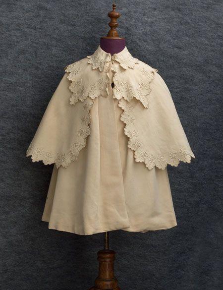 Child's embroidered silk coat with cape, circa 1910.