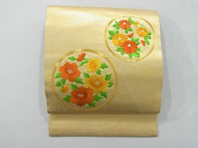 This is an elegant Nagoya obi with flower circle design. It has been embroidered botan(peony) and kiku(chrysanthemum) flowers brightly