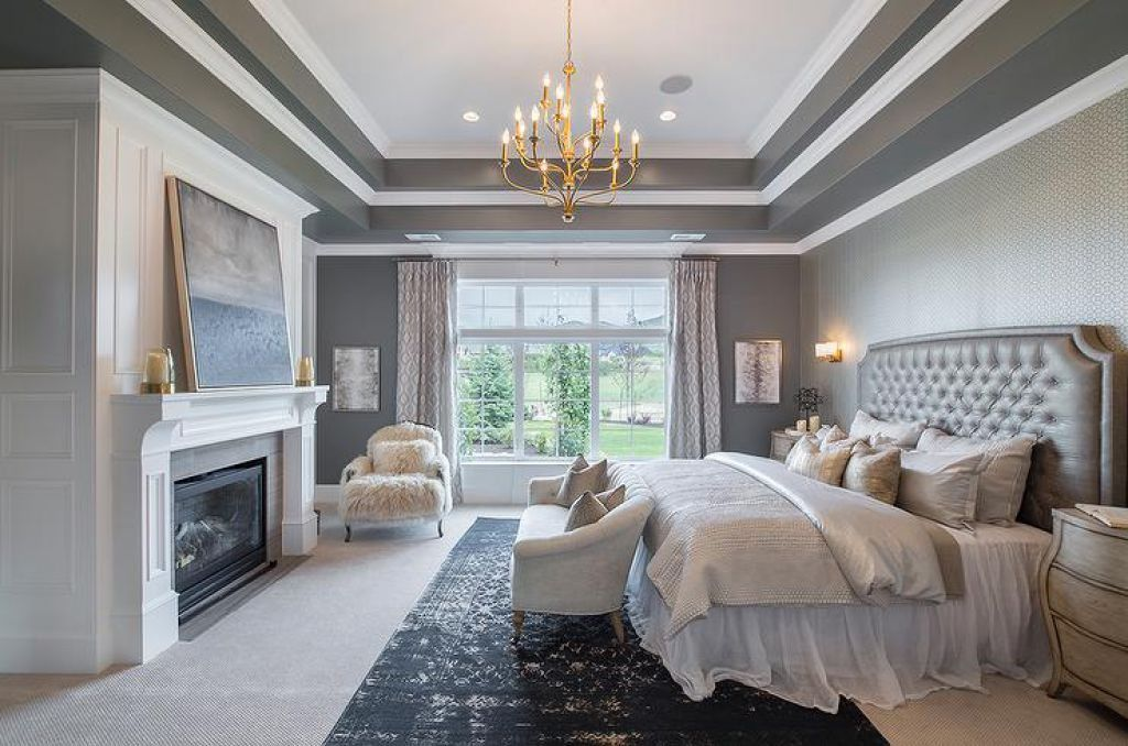 Gray Bedroom Designed With Tray Ceiling And Chandelier
