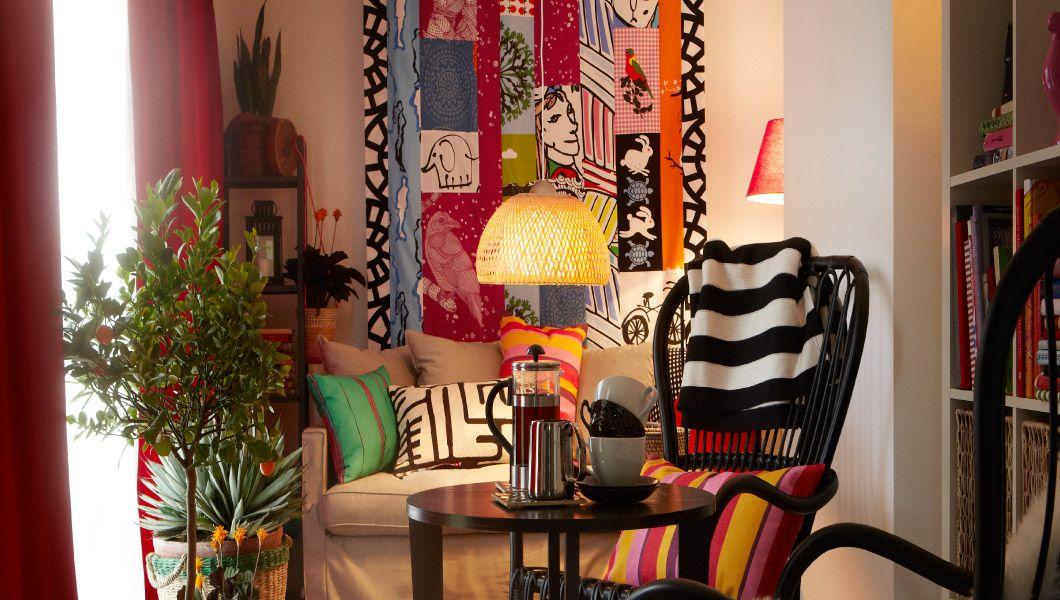"""Stoff in Hülle und Fülle; ein kleines, kuscheliges Wohnzimmer mit HÄRNÖSAND 3er-Sofa mit Bezug """"Olstorp"""" sandfarben und schwarzem STORSELE Sessel mit hoher Rückenlehne aus Rattan mit vielen Textilien wie bunten EIVOR Kissen, Kissen mit VALBORG Kissenbezug rotlila/orange und EIVOR Plaid schwarz/weiß"""