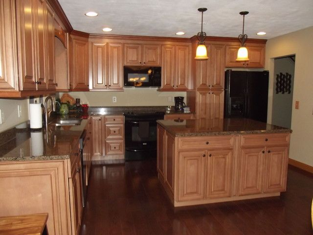 maple kitchen cabinets with dark wood floors, dark countertops