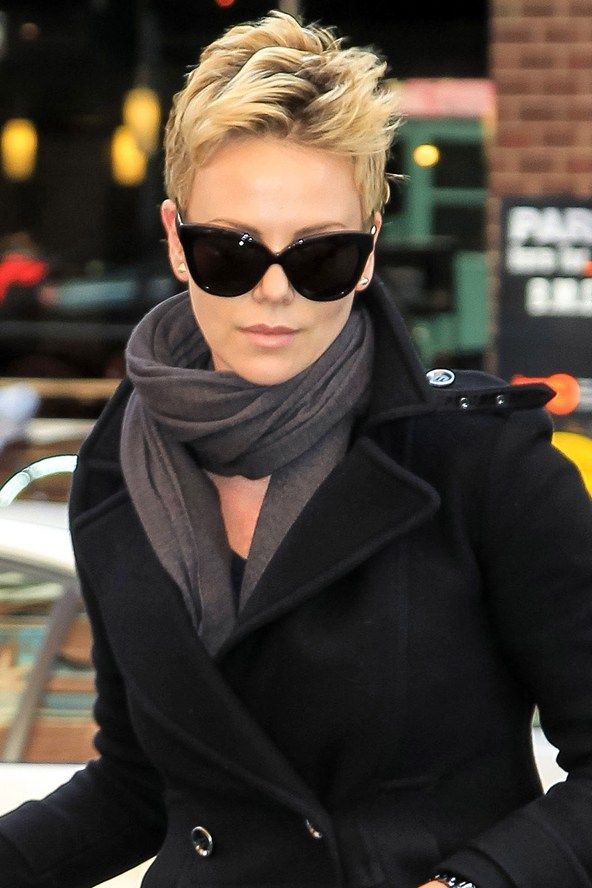 ba61518dd6bd0 Charlize is looking more gorgeous than ever with her spiked-up bleached  crop and over-sized shades.