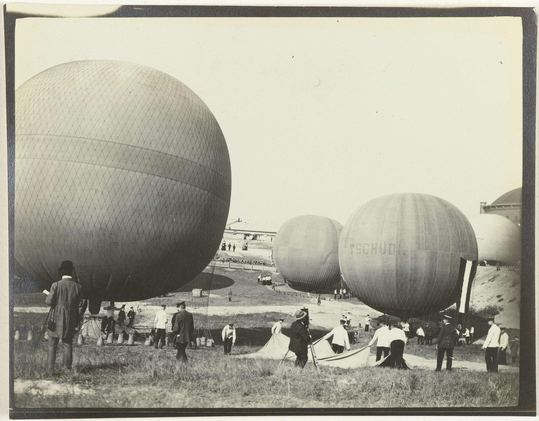 Anonymous | De derde Gordon Bennett ballonrace, Anonymous, 1908 | Vier opgeblazen ballonnen aan de grond. Mensen bezig met voorbereidingen. In het midden een fotograaf. Op een van de ballonnen de letters TSCHUD.