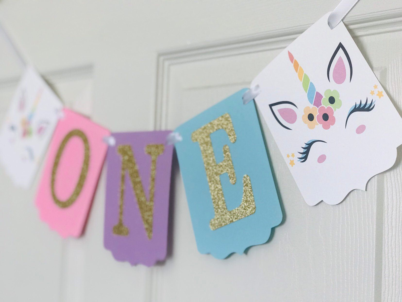 Unicorn Theme One Banner Unicorn Theme High Chair Banner Unicorn Theme 1st Birthday Banner Unicorn Party Decoration Unicorn High Chair - Unicorn party decorations, Kids birthday party decoration, 1st birthday banners, Unicorn theme party, Unicorn party, Birthday banner - One High Chair Banner that would look great on your upcoming Unicorn Theme Party   Current PROCESSING TIME is about 24 business days after purchase then will ship via USPS First Class (35 business days) If you need it sooner, pls  message me   Each panel is 5 5  tall and 4  wide  Banner is made from high quality premium cardstock and strung with a white satin ribbon  Letters are made from gold glitter cardstock  Banner comes assembled and ready to hang Want a different color of cardstock  just message me, I'll be glad to assist you  Thank you for stopping by!