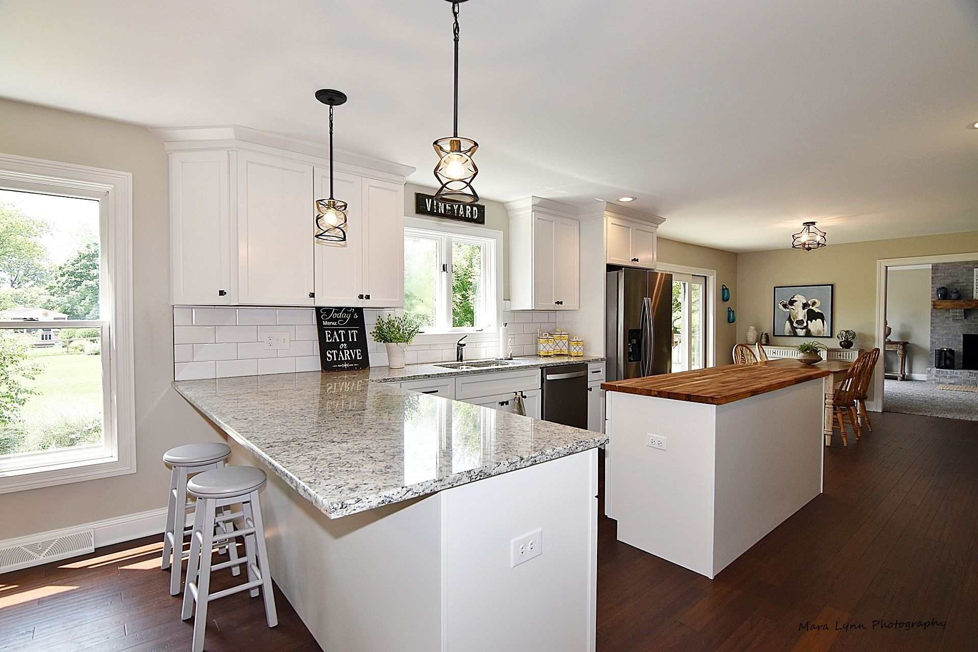 White kitchen with both an island and peninsula with ...