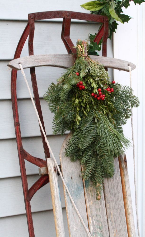 Swag tied to an old sled leaned against the house. A great Christmas decorating idea.