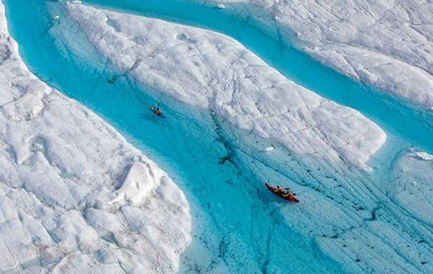 Kayaking The Blue River Created By The Melting Petermann Glaciers In