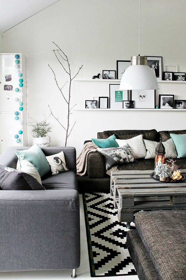 Modern scandinavian inspired living room with some turquoise pillows great black and white rug