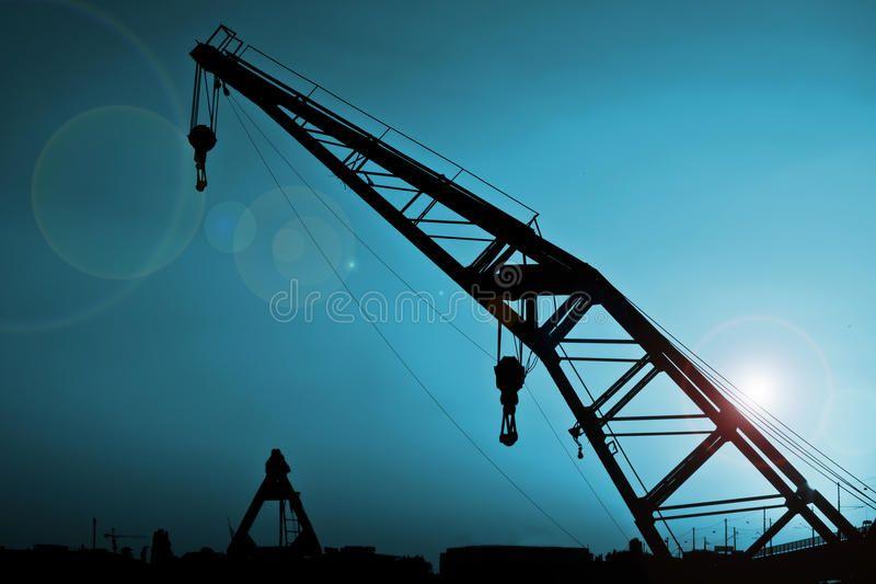 Crane Silhouette over blue sky and lens flair