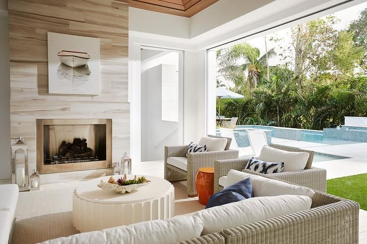 Covered deck with a white and brown stone fireplace