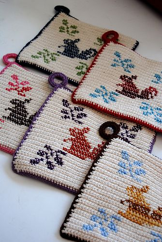 """here are the potholders that i made for this year's swap.  despite the """"claw hand"""" i really got a kick out of this experiment and i hope the recipients like them.  the concept isn't very complicated -- just 2 squares of single crochet with a simple design cross stitched on one  -- but each one took forever."""