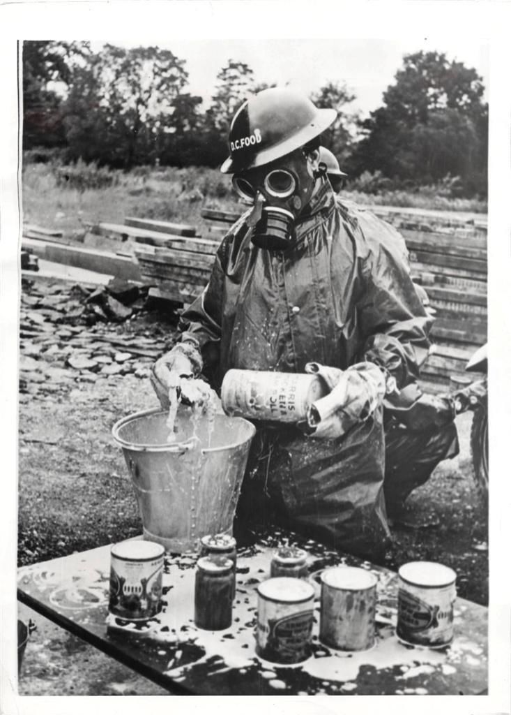 1941 member of a decontamination squad swabs cans of food with a bleach cream after they were splashed with mustard gas at britain s first food
