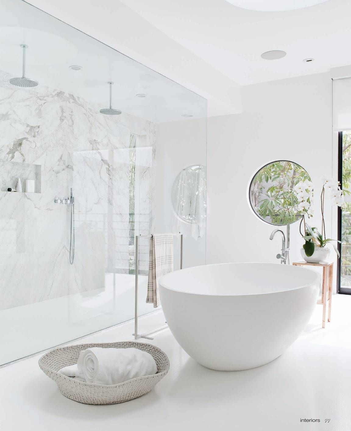 Photo of Marble Wall, glass shower enclosure, round window, teacup tub – great design. Co…
