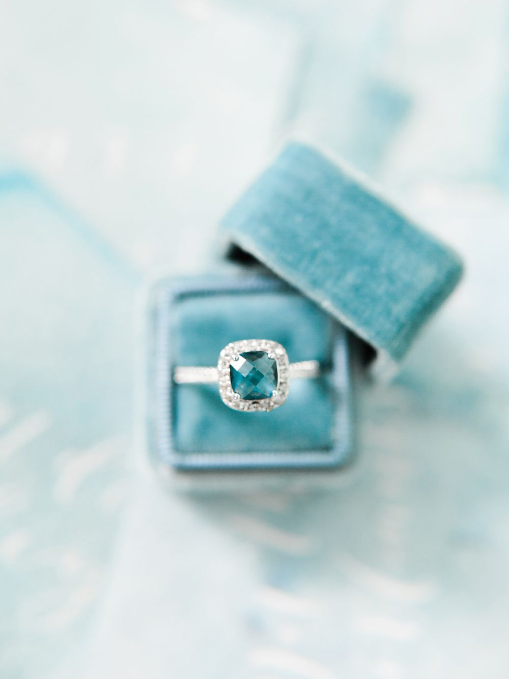 Engagement ring in a blue velvet ring box by The Mrs Box Image by