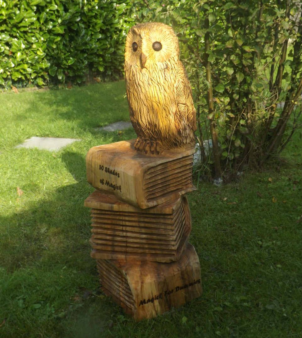 A chainsaw carved owl perched on books my