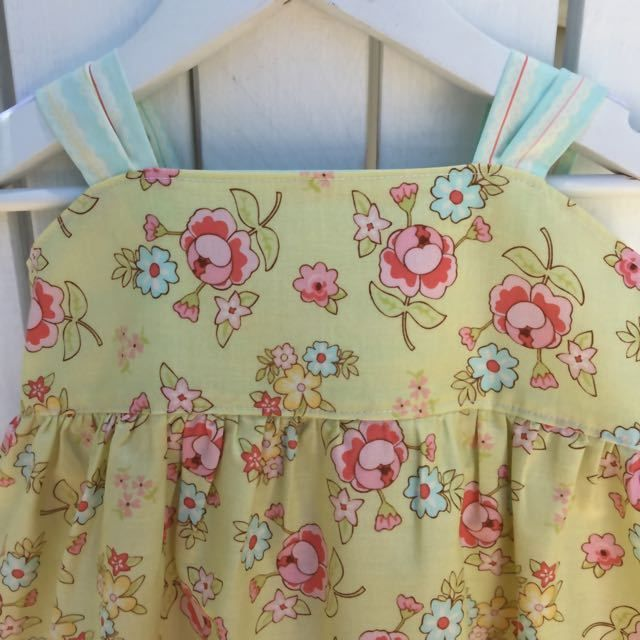 This dress is made from high quality 100% CottonThe main fabric is a soft green with pink and aqua roses.It is nicely complimented by the coordinating lace print fabricThe Dress has a fitted bodice with an elasticated back. This plus the adjustable bow makes it a great fit on most body shapes.*measurements (to indicate length) have been taken from under the arms and down the side of the dress to the hem ...size 5 - 57cm