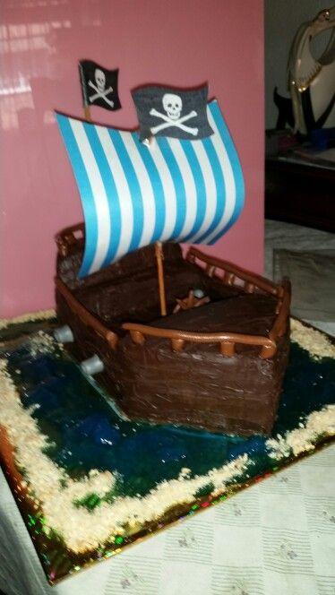 Tarta barco , bizcochuelo bañado en almibar de vainilla y relleno de buttercream de nocilla y buttercream de dulce de leche von queso crema y por fuera ganache de chocolate negro y adornos en fondant de chocolate
